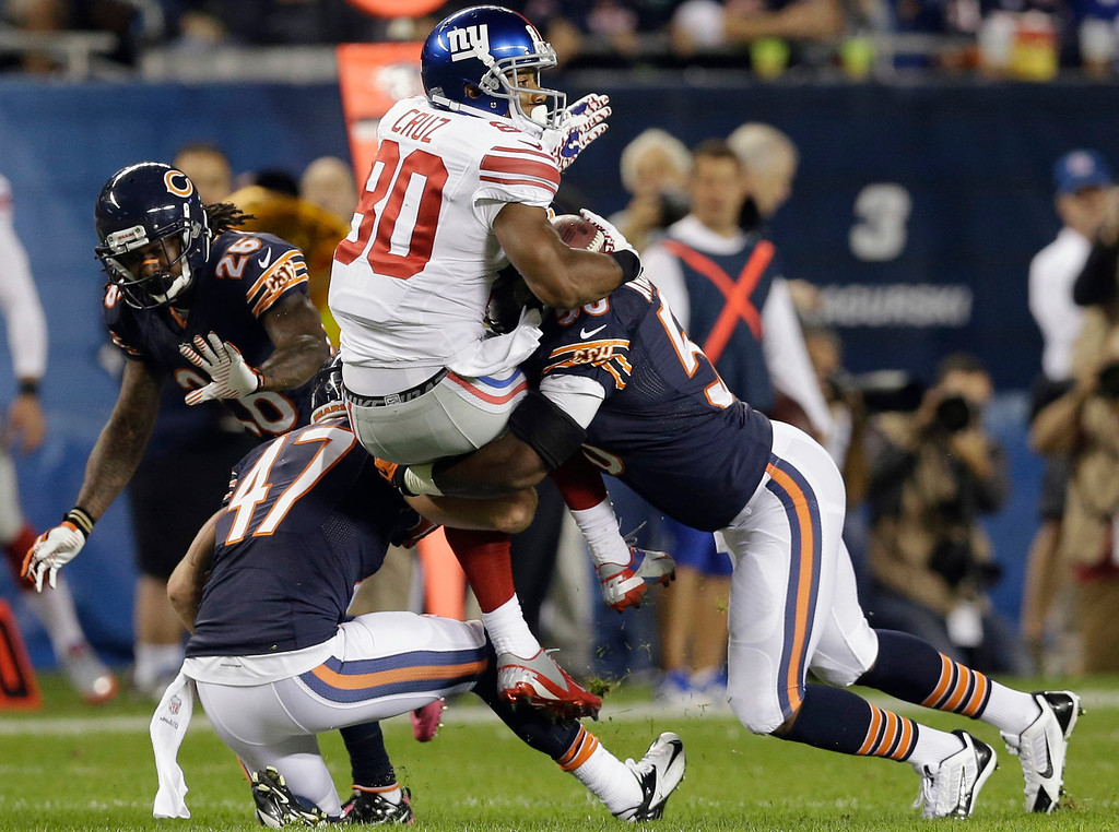 . New York Giants wide receiver Victor Cruz (80) is tackled by Chicago Bears safety Chris Conte (47) and linebacker James Anderson (50) in the first half of an NFL football game, Thursday, Oct. 10, 2013, in Chicago. (AP Photo/Nam Y. Huh)