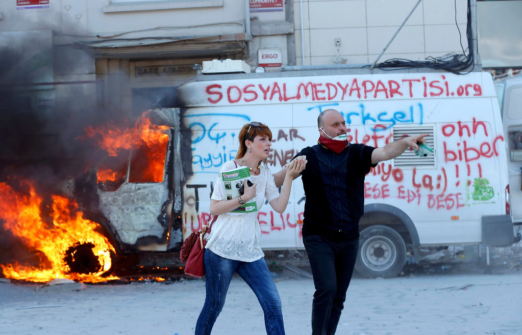 . A protester helps a woman as she passes next to a burning bus during a protest at Taksim Square in Istanbul June 11, 2013.  REUTERS/Murad Sezer