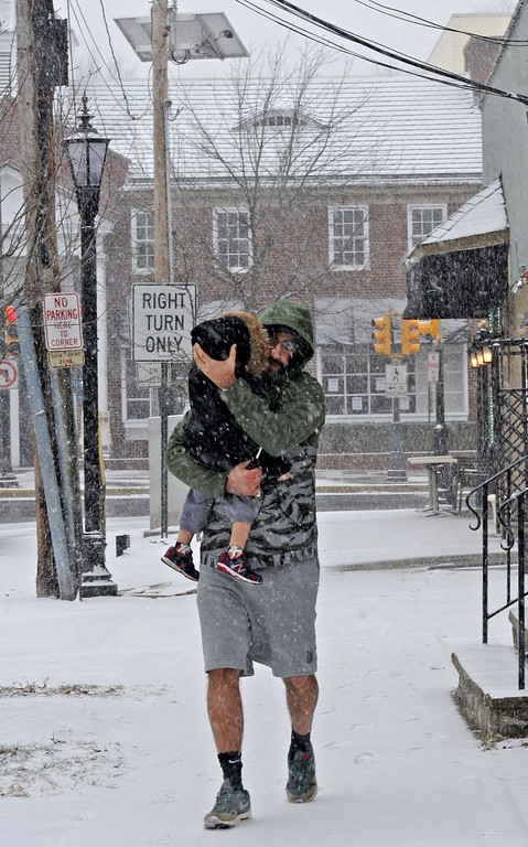 . Vincent DiPalm tries to protect his son, Rocco, 2, from falling snow in Haddonfield, NJ, on Tuesday, Jan. 21, 2014. (April Saul/Philadelphia Inquirer/MCT)