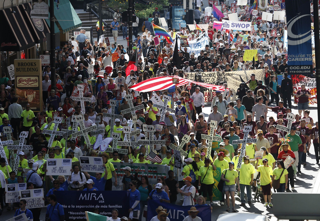 . Immigrants and activists march during a rally in Chicago, Wednesday, May 1, 2013. Thousands of marchers have made their way through downtown Chicago to a rally in support of easing the nation\'s immigration laws. (AP Photo/Charles Rex Arbogast)
