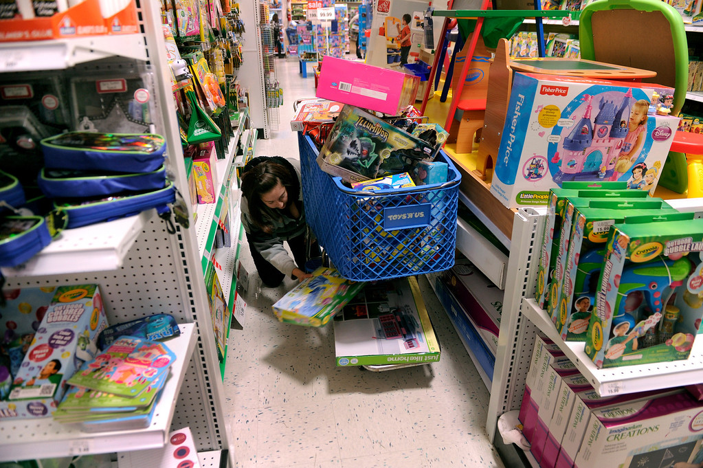. Jennifer Martinez searched for room to put more toys as she filled a cart with items at the Toys R Us store on County Line Road in Arapahoe County and the Best Buy store in Lone Tree Thursday night, November 28, 2013. Many metro area stores got a jump on Black Friday by opening Thanksgiving night. Photo By Karl Gehring/The Denver Post