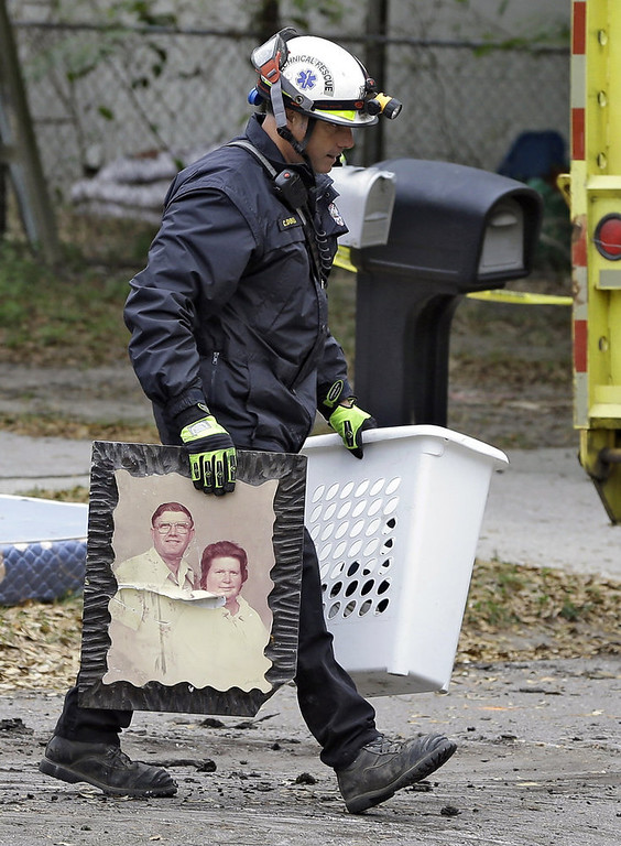 . A Hillsborough County, Fla., firefighter removes salvaged items, including a family photo, from the home where a sinkhole swallowed Jeffrey Bush, late Thursday in Seffner, Fla., on Sunday, March 3, 2013. Crews are set to begin the demolition of the home on Sunday, after search personnel failed to find Bush. (AP Photo/Chris O\'Meara)