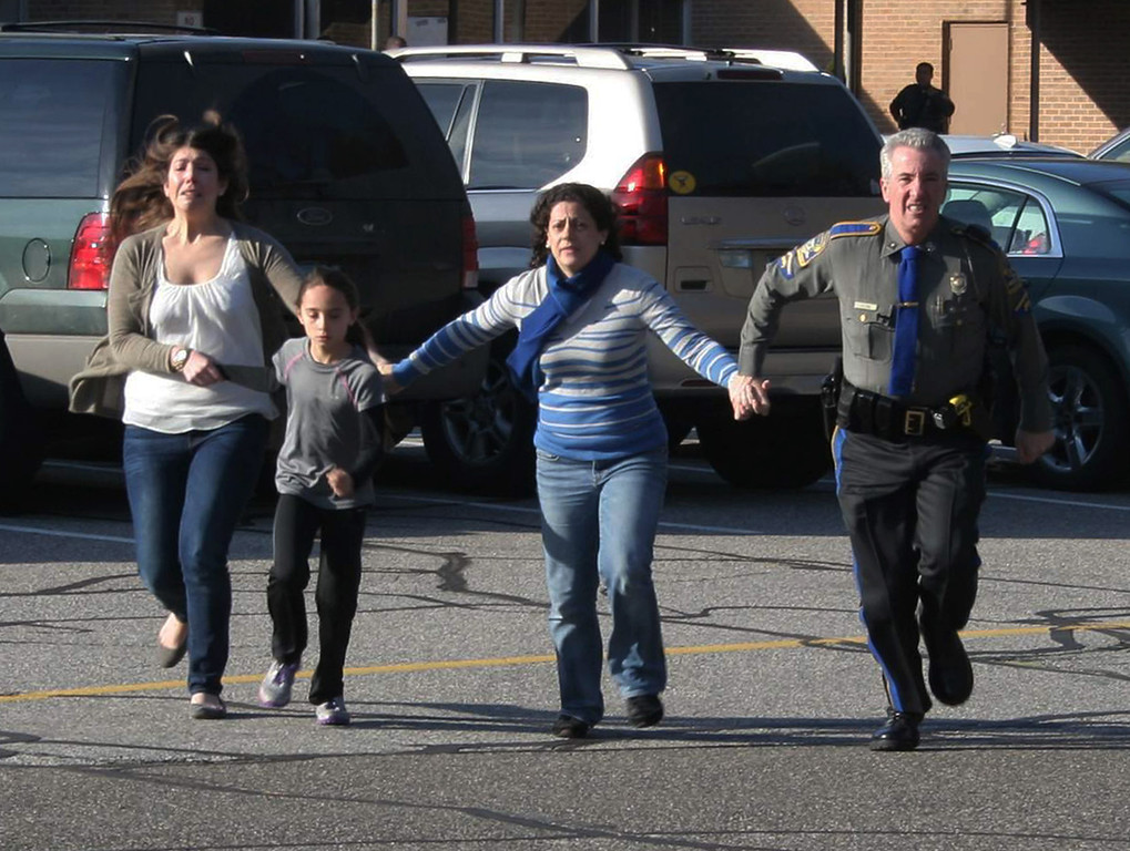 . In this photo provided by the Newtown Bee, a police officer leads two women and a child from Sandy Hook Elementary School in Newtown, Conn., where a gunman opened fire, killing 26 people, including 20 children, Friday, Dec. 14, 2012. (AP Photo/Newtown Bee, Shannon Hicks)
