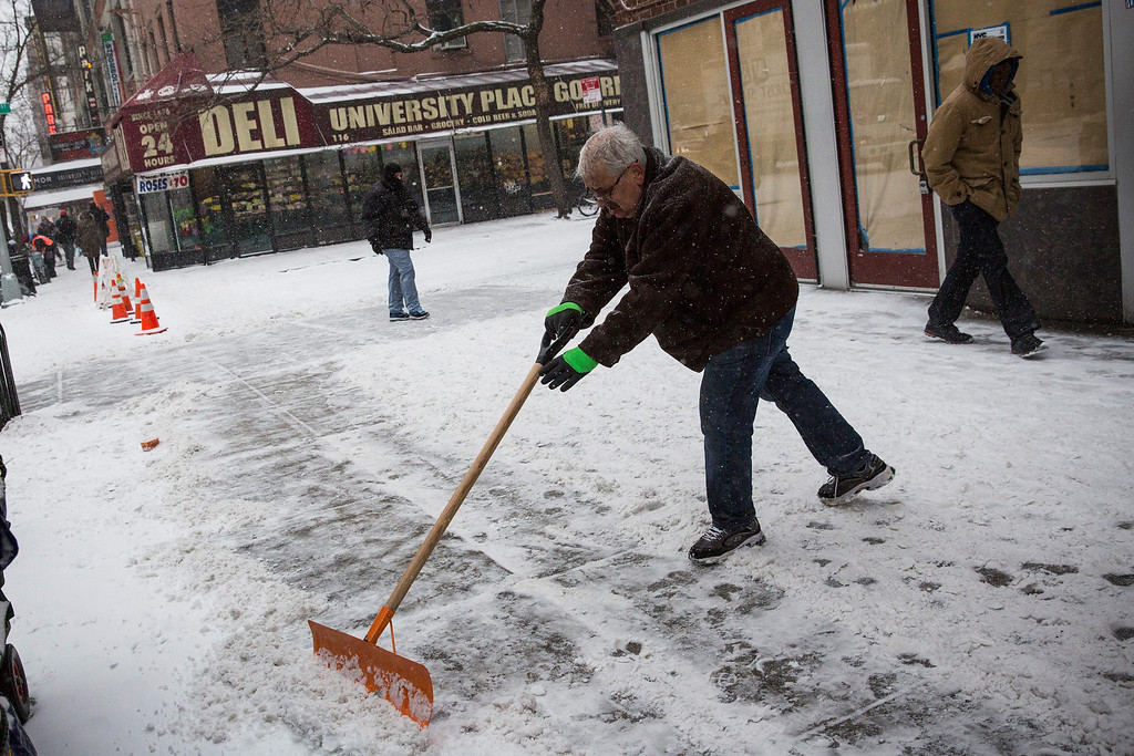 . A man shovels snow from a snowstorm that is moving through the Northeast on January 21, 2014 in New York City.   (Photo by Andrew Burton/Getty Images)