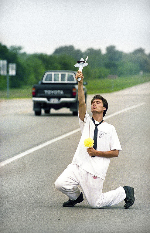 . James Michael Lesak, 20, of Houston, holds a cross and an artificial flower as he stages what he said was a protest over the February 28 shooting at the Branch Davidian compound near Waco, Texas on Tuesday, April 14, 1993. (AP Photo/Rick Bowmer)