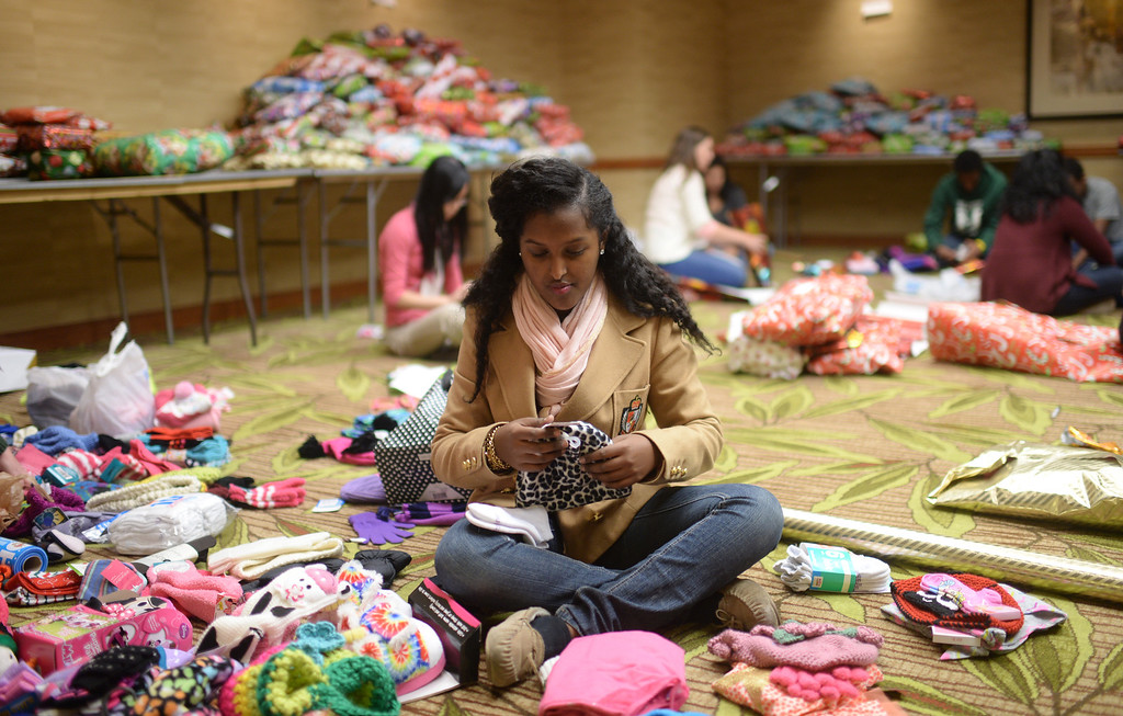 """. DENVER, CO. DECEMBER 21: Sara Dessie, 17, of Denver is wrapping Christmas gift during the annual Father Woody Christmas Party in Denver, Colorado December 21, 2013. In advance of handing out 5,000 gifts, volunteers are doing a \""""wrapping party\"""" at the Sheraton Denver Downtown Hotel. (Photo by Hyoung Chang/The Denver Post)"""