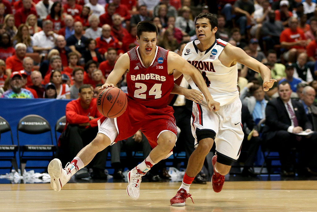 . Bronson Koenig #24 of the Wisconsin Badgers is fouled by Elliott Pitts #24 of the Arizona Wildcats in the first half during the West Regional Final of the 2014 NCAA Men\'s Basketball Tournament at the Honda Center on March 29, 2014 in Anaheim, California.  (Photo by Jeff Gross/Getty Images)