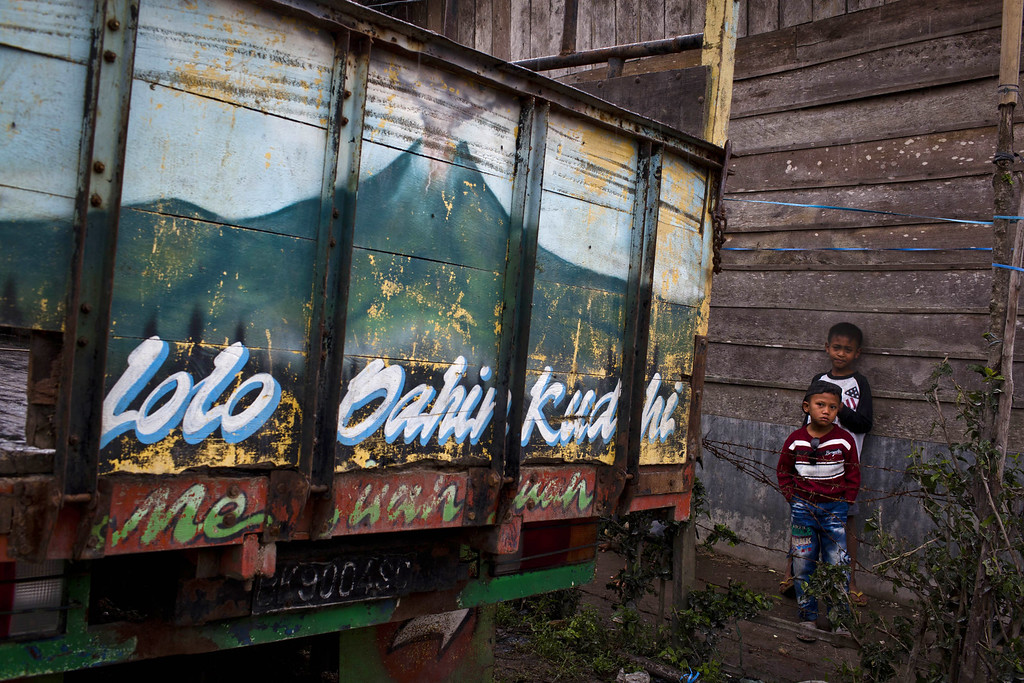 . Children stand beside a house as painting of mount Sinabung erupts is seen on a truck in Suka Nalu village on November 15, 2013 in Karo district, South Sumatra, Indonesia. Up to 4,300 residents have been evacuated from five villages in North Sumatra due to the volcanic eruptions of Mount Sinabung. (Photo by Ulet Ifansasti/Getty Images)