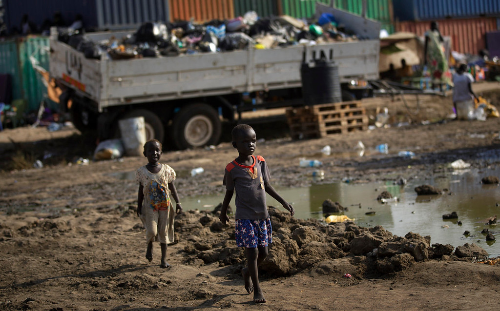 . Displaced children walk inside a United Nations compound which has become home to thousands of people displaced by the recent fighting, in the capital Juba, South Sudan Sunday, Dec. 29, 2013. Some 25,000 people live in two hastily arranged camps for the internally displaced in Juba and nearly 40,000 are in camps elsewhere in the country, two weeks after violence broke out in the capital and a spiralling series of ethnically-based attacks coursed through the nation, killing at least 1,000 people. (AP Photo/Ben Curtis)