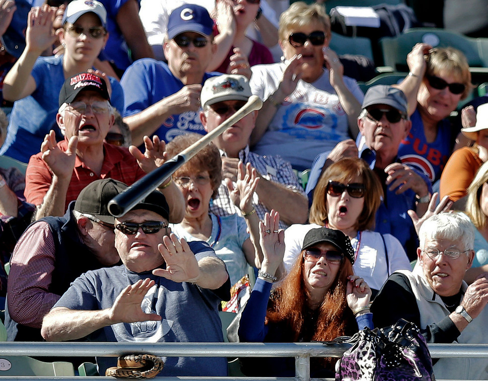 . Fans try to get out of the way after Chicago Cubs\' Christian Villanueva lost his bat during the fifth inning of an exhibition spring training baseball game against the Colorado Rockies, Tuesday, Feb. 26, 2013, in Phoenix. (AP Photo/Morry Gash, File)