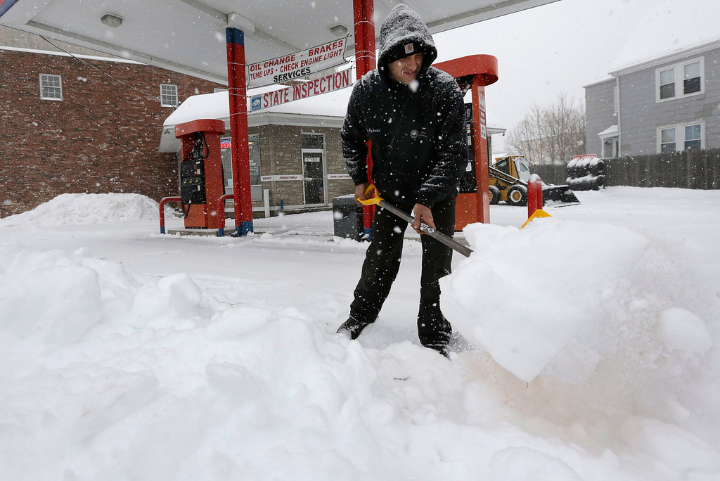 . Andrew Pyliotis, of Wrentham, Mass., shovels snow in front of his gas station in Norwood, Mass., Wednesday, Feb. 5, 2014.  Six to 12 inches of snow is expected around Boston, with 3 to 6 inches in southeastern areas before changing to sleet and rain. (AP Photo/Steven Senne)