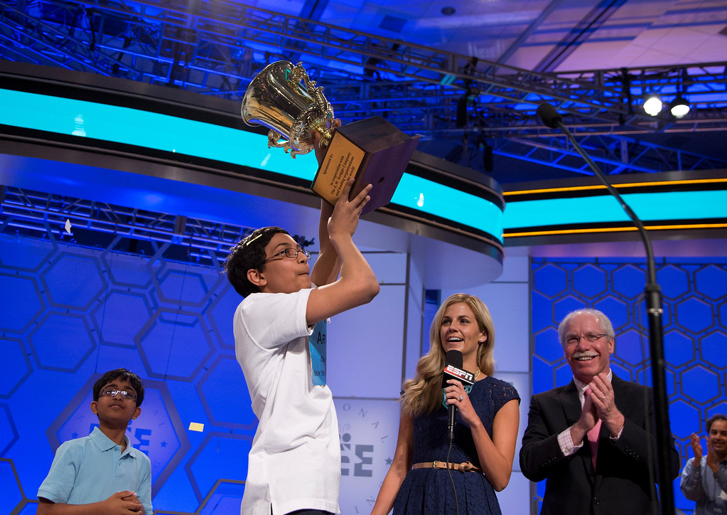 """. Arvind Mahankali, 13, of Bayside Hills, N.Y., lifts the championship trophy after he won the National Spelling Bee by spelling the word \""""knaidel\"""" correctly on Thursday, May 30, 2013, in Oxon Hill, Md. (AP Photo/Evan Vucci)"""
