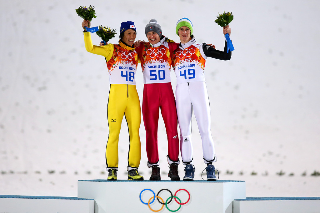 . SOCHI, RUSSIA - FEBRUARY 15:  (L-R) Silver medalist Noriaki Kasai of Japan, gold medalist Kamil Stoch of Poland and bronze medalist Peter Prevc of Slovenia celebrate on the podium during the flower ceremony after the Men\'s Large Hill Individual Final Round on day 8 of the Sochi 2014 Winter Olympics at the RusSki Gorki Ski Jumping Center on February 15, 2014 in Sochi, Russia.  (Photo by Julian Finney/Getty Images)
