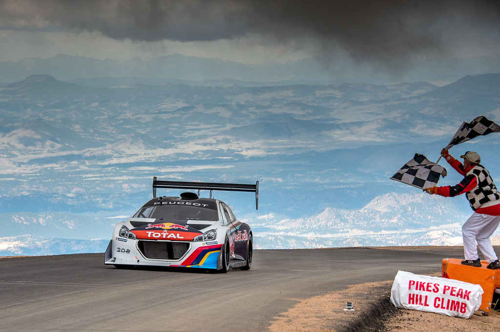 . Nine-time WRC world champion Sebastien Loeb of France crosses the finish line with his Peugeot 208 T16 at the top of Pikes Peak mountain during the Pikes Peak International Hill Climb (PPIHC) at Pike National Forest, 10 miles(16 km) west of Colorado Springs, Colorado, on June 30, 2013. The Pikes Peak International Hill Climb (PPIHC), also known as The Race to the Clouds, an annual automobile and motorcycle hillclimb to the summit of Pikes Peak. The track measures 12.42 miles (19.99 km) over 156 turns, climbing 4,720 ft (1,440 m) from the start to the finish at 14,110 ft (4,300 m), on grades averaging 7 percent.     JOE KLAMAR/AFP/Getty Images