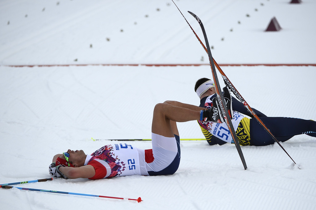 . Norway\'s Chris Andre Jespersen lies on the snow after crossing the finish line in the Men\'s Cross-Country Skiing 15km Classic at the Laura Cross-Country Ski and Biathlon Center during the Sochi Winter Olympics on February 14, 2014 in Rosa Khutor near Sochi.  The tough men\'s 15 km classic time trial saw apparel not usually associated with skiing, with many competitors wearing just T-shirts instead of the normal long-sleeves while others even bared their legs.  AFP PHOTO / PIERRE-PHILIPPE MARCOU/AFP/Getty Images