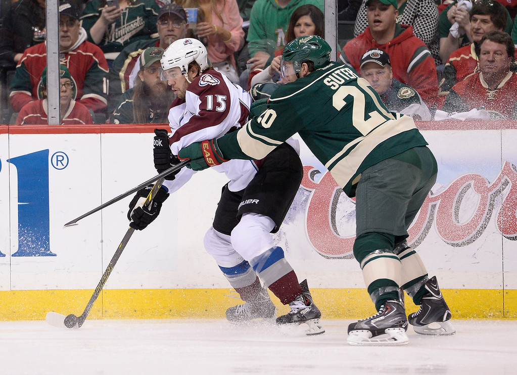 . Colorado Avalanche right wing P.A. Parenteau (15) works with the puck as Minnesota Wild defenseman Ryan Suter (20) comes in on defense during the first period April 28, 2014 in Game 6 of the Stanley Cup Playoffs at Xcel Energy Center.  (Photo by John Leyba/The Denver Post)