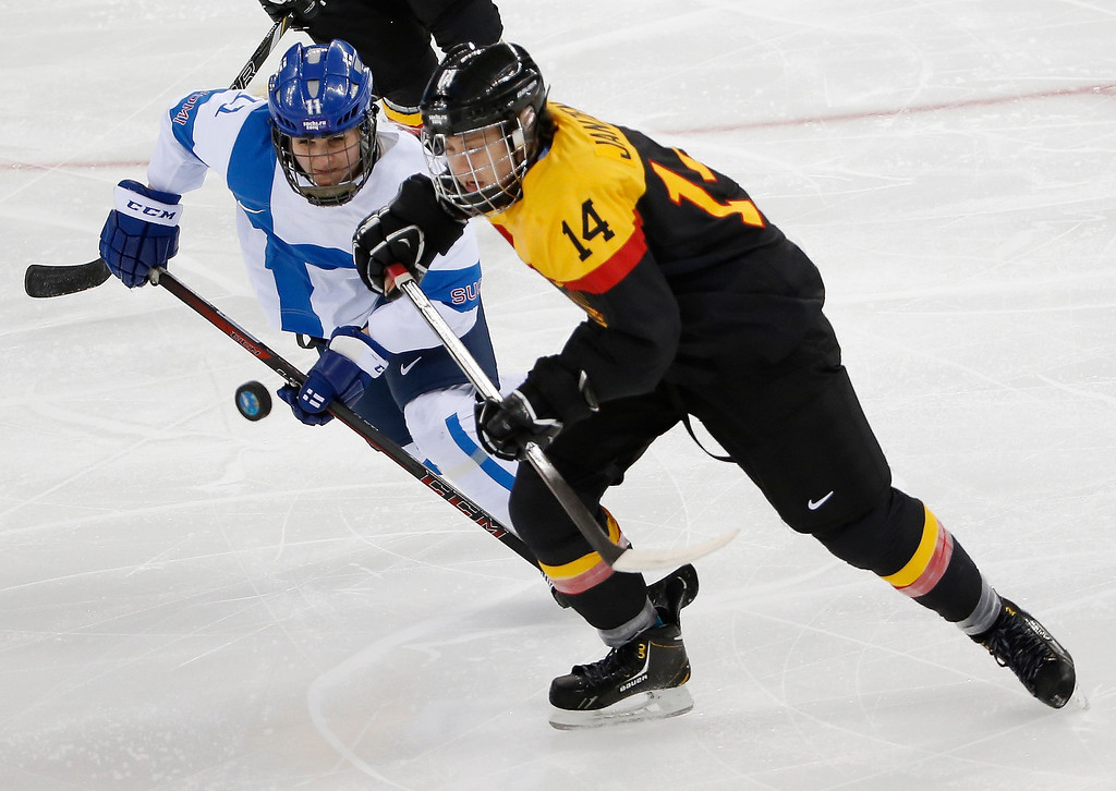 . Annina Rajahuhta of Finland and Jacqueline Janzen of Germany chase a loose puck during the 2014 Winter Olympics women\'s ice hockey game at Shayba Arena, Sunday, Feb. 16, 2014, in Sochi, Russia. (AP Photo/Petr David Josek)