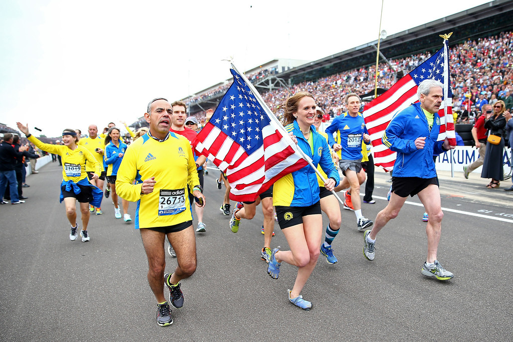 . Runners who participated in the 2013 Boston Marathon run down pit road during the IZOD IndyCar Series 97th running of the Indianpolis 500 mile race at the Indianapolis Motor Speedway on May 26, 2013 in Indianapolis, Indiana.  (Photo by Michael Hickey/Getty Images)
