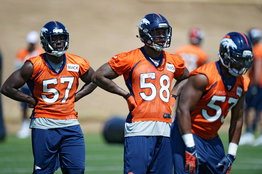 . Denver Broncos Lamin Barrow (57) and Von Miller (58) watch drills during OTAs June 11, 2014 at Dove Valley. (Photo by John Leyba/The Denver Post)