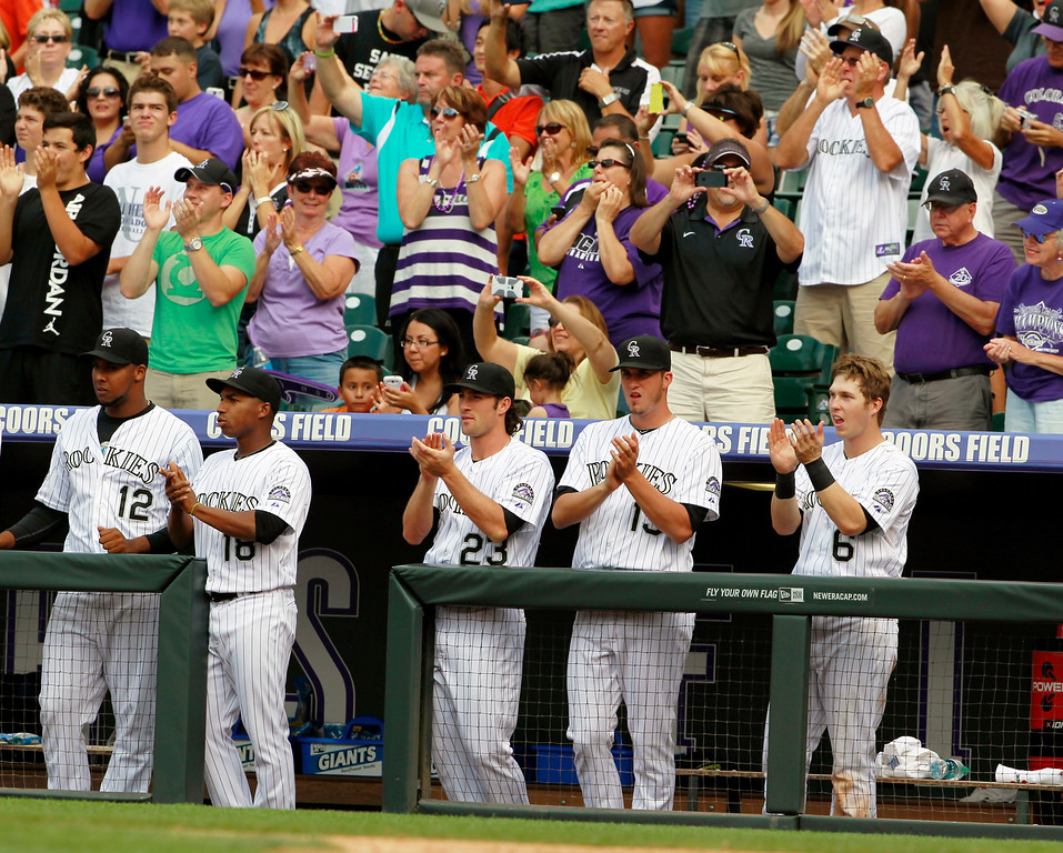 . Members of the Colorado Rockies crowd the rail in the dugout to join fans in applauding after the Rockies\' Todd Helton connected for a double to notch his 2,500th career hit against the Cincinnati Reds in the seventh inning of the Rockies\' 7-3 victory in a baseball game in Denver on Sunday, Sept. 1, 2013. (AP Photo/David Zalubowski)
