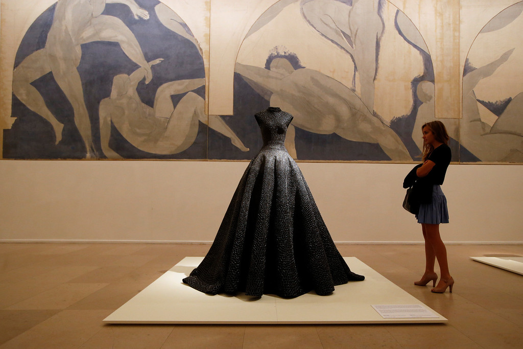 ". A visitor, Una Duval age 21, looks at ""Long Dress\"" of woven raffia, silver thread and bead embroidery of Spring Summer 1997 collections by French Tunisian born Fashion designer Azzedine Alaia, presented for the first Paris retrospective of couturier front of \""Lutte des Nymphes\"", 1931 by Matisse at the Museum of Modern Art in Paris, Wednesday, Sept. 25, 2013. A selection of seventy iconic models retracing a unique creative career of Alaia are displayed for the reopening of the Galliera Museum and in the Matisse room at the Museum of Modern Art of Paris. (AP Photo/Francois Mori)"