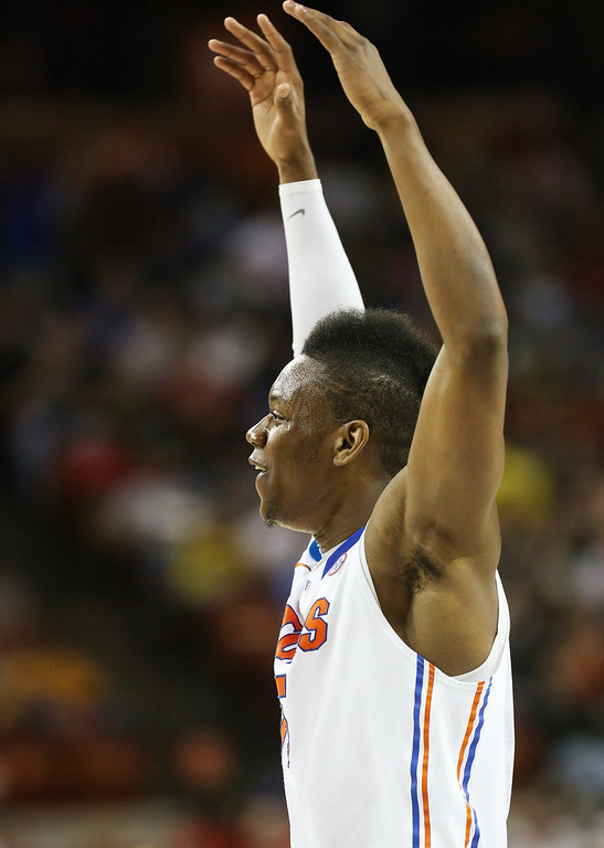 . Will Yeguete #15 of the Florida Gators celebrtates after a teammate scored in the first half against the Minnesota Golden Gophers during the third round of the 2013 NCAA Men\'s Basketball Tournament at The Frank Erwin Center on March 24, 2013 in Austin, Texas.  (Photo by Stephen Dunn/Getty Images)