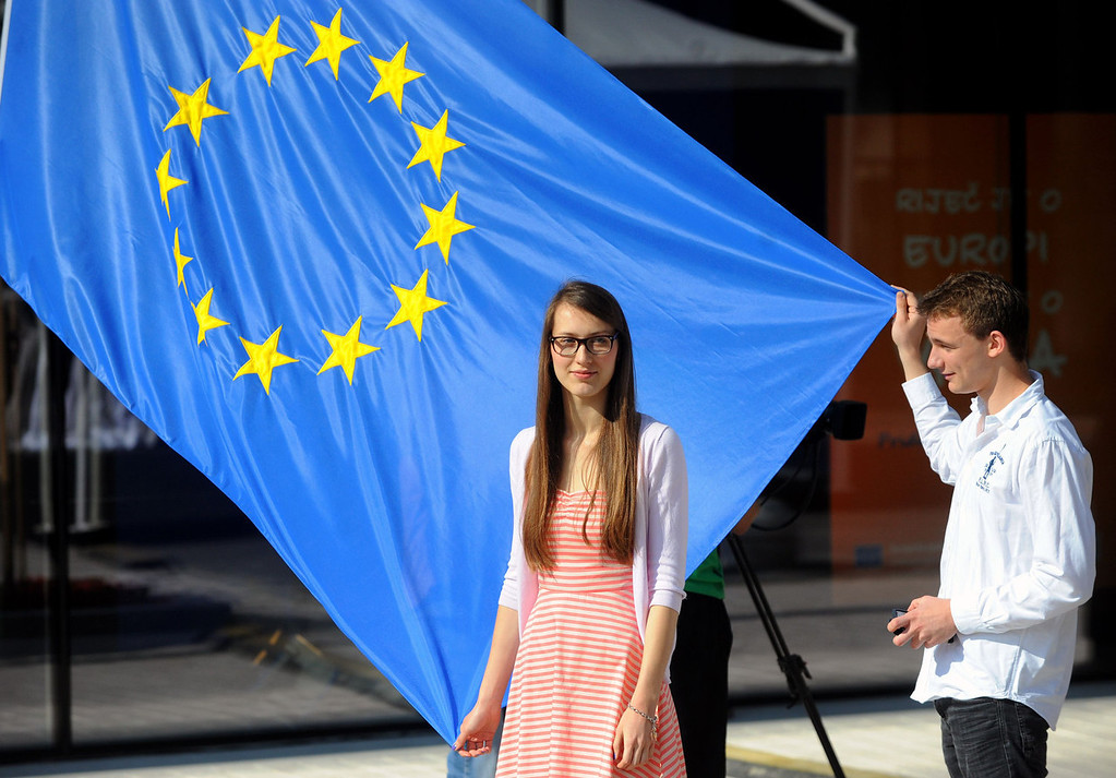. A Croatian teenager holds an EU flag during the opening ceremony of the European Union office in Zagreb on July 1, 2013. Croatia woke up on Monday as the newest EU state after a night of celebrations dampened by fears that membership to the crisis-hit bloc would only add to the country\'s deep-rooted economic burden.  STRINGER/AFP/Getty Images