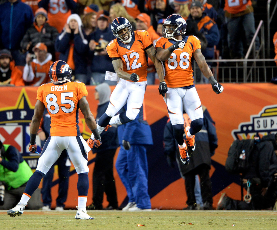 . Denver Broncos wide receiver Andre Caldwell (12) celebrates his first quarter touchdown with Denver Broncos wide receiver Demaryius Thomas (88).  The Denver Broncos vs. the San Diego Chargers at Sports Authority Field at Mile High in Denver on December 12, 2013. (Photo by Hyoung Chang/The Denver Post)