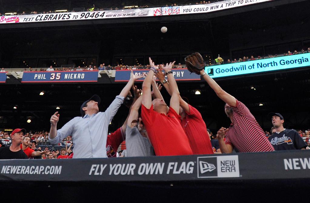 . Baseball fans behind the Atlanta Braves dugout reach for a foul ball hit by Atlanta\'s Chris Johnson during the second inning of a baseball game against the Colorado Rockies Friday, May 23, 2014, in Atlanta. (AP Photo/David Tulis)