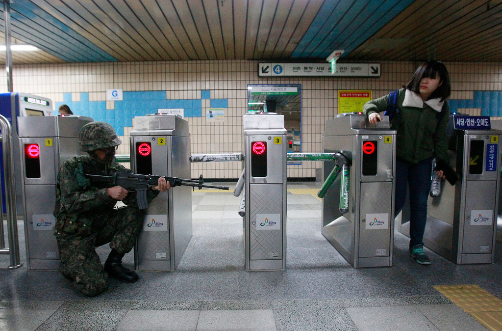 . A South Korean army soldier aims his machine gun as a passenger passes by a ticket barrier during an anti-terrorism drill against possible terrorists\' attacks at a subway station in Seoul, South Korea, Monday, April 15, 2013. Oblivious to international tensions over a possible North Korean missile launch, Pyongyang residents spilled into the streets Monday to celebrate a major national holiday, the birthday of their first leader, Kim Il Sung. (AP Photo/Ahn Young-joon)
