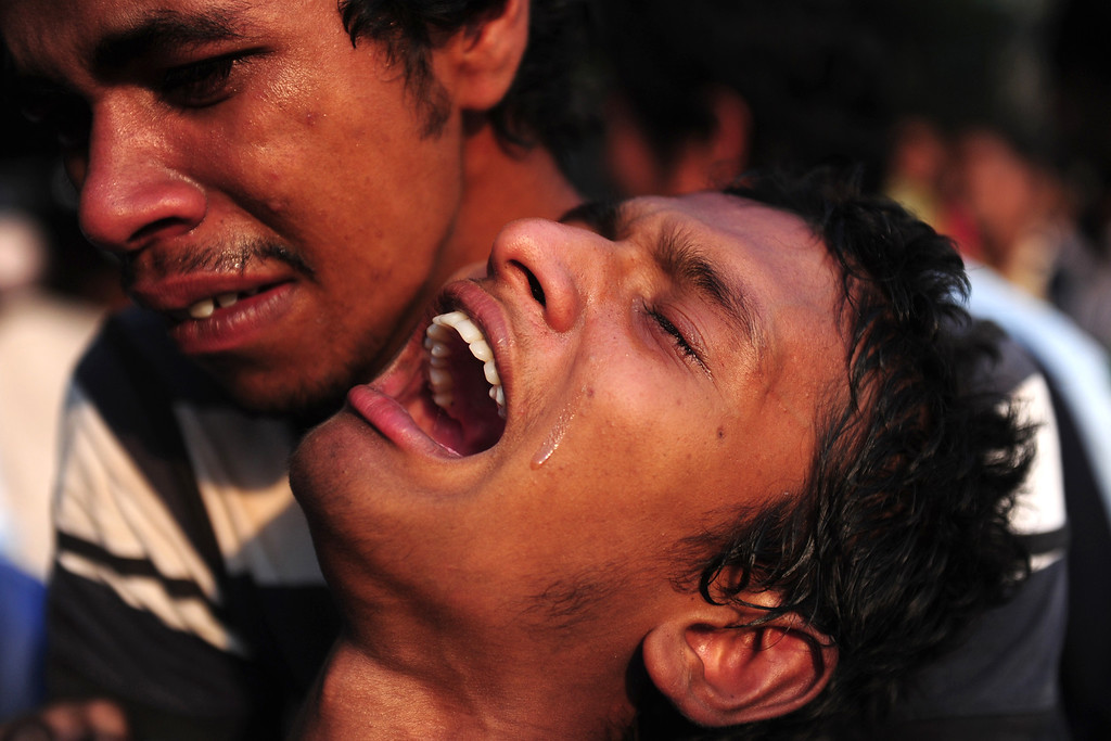 . A Bangladeshi youth reacts after seeing his relatives dead body after a building collapse in Savar, on the outskirts of Dhaka, on April 24, 2013.  AFP PHOTO/ Munir uz ZAMAN/AFP/Getty Images