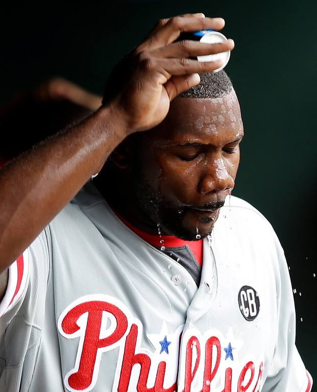 . Philadelphia Phillies\' Ryan Howard douses himself with water during the fourth inning of an opening day baseball game against the Texas Rangers at Globe Life Park, Monday, March 31, 2014, in Arlington, Texas.  (AP Photo/Tony Gutierrez)