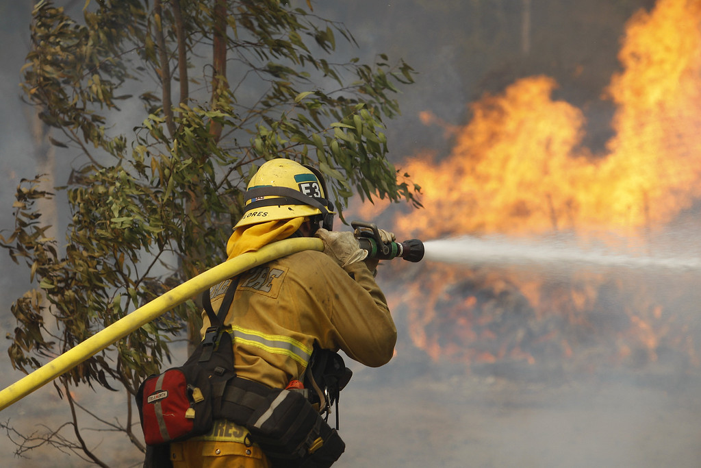 . A firefighter hoses flames at the Cocos fire on May 15, 2014 in San Marcos, California. Fire agencies throughout the state are scrambling to prepare for what is expected to be a dangerous year of wildfires in this third year of extreme drought in California.   (Photo by David McNew/Getty Images)