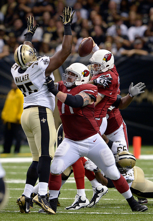 . Arizona Cardinals quarterback Carson Palmer (3) is sacked by New Orleans Saints outside linebacker Junior Galette (93) as Cardinals guard Daryn Colledge (71) blocks out Saints defensive end Tyrunn Walker (75) in the first half of an NFL football game in New Orleans, Sunday, Sept. 22, 2013. (AP Photo/Bill Feig)
