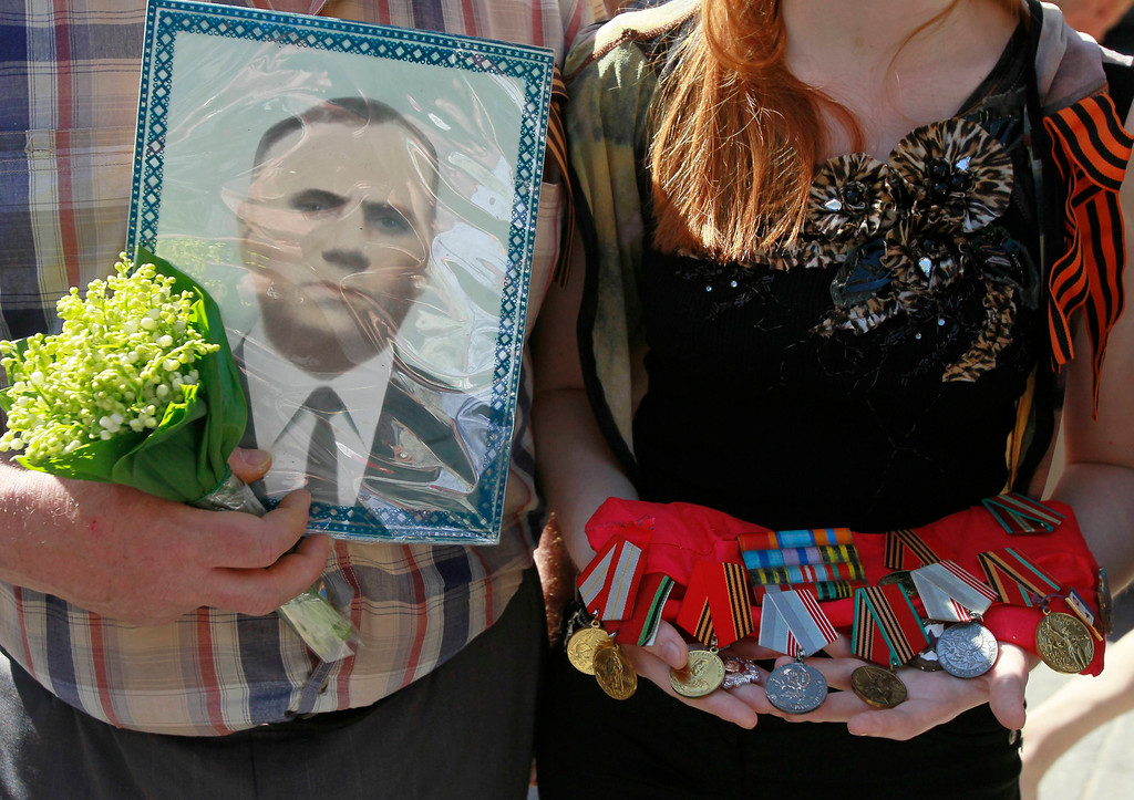 ". People holding a portrait and medals of their relative who died after World War Two march in an improvised ""Victory Day march\"" to pay homage to their loved ones in Kiev May 9, 2013. Ukraine commemorates the 68th anniversary of the Soviet Union\'s victory over Nazi Germany on May 9.  REUTERS/Gleb Garanich"