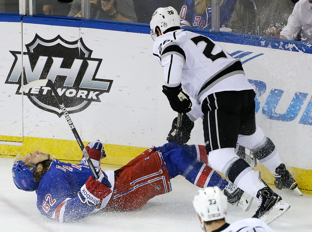 . New York Rangers left wing Carl Hagelin (62) loses his footing against Los Angeles Kings defenseman Slava Voynov (26) in the first period during Game 3 of the NHL hockey Stanley Cup Final, Monday, June 9, 2014, in New York. (AP Photo/Frank Franklin II)