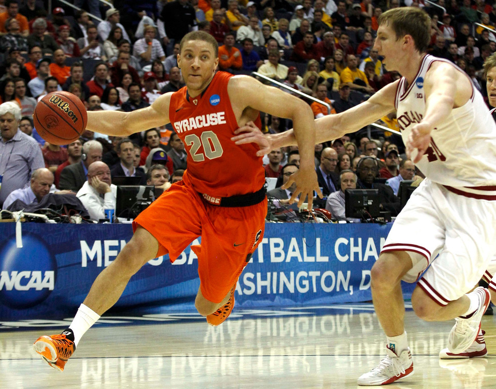 . Syracuse Orange guard Brandon Triche (L) drives past Indiana Hoosiers forward Cody Zeller during the second half in their East Regional NCAA men\'s basketball game in Washington, March 28, 2013. REUTERS/Larry Downing