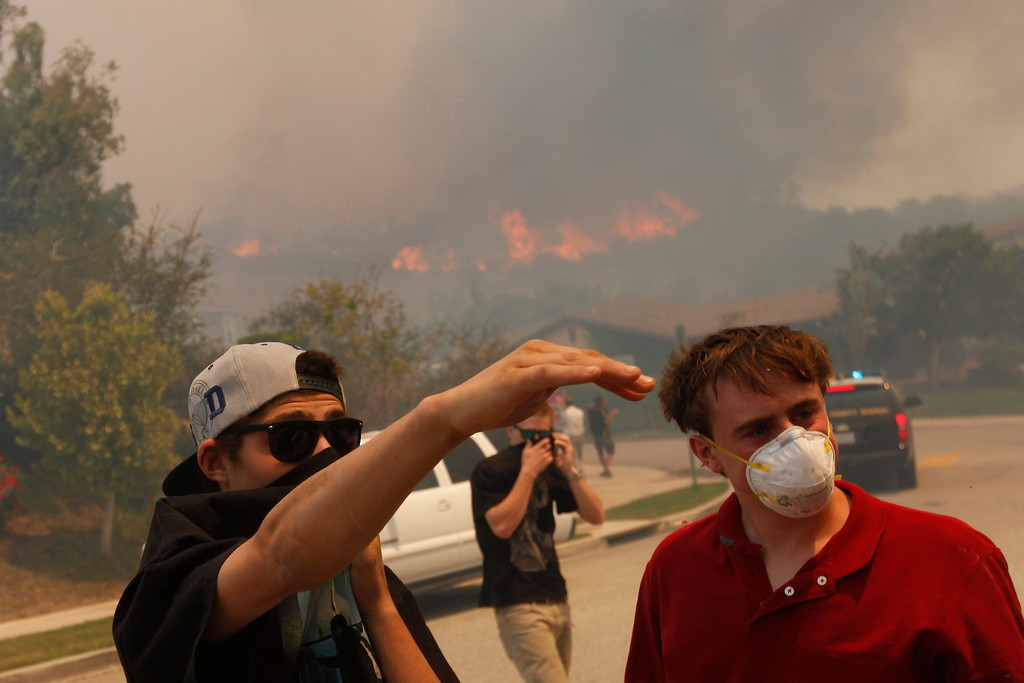 . People near homes on Calle Del Prado watch a fast-moving brush fire in the Newbury Park area of Ventura County May 2, 2013. REUTER/Patrick T. Fallon