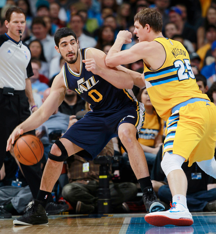 . Utah Jazz center Enes Kanter, left, of Turkey, works ball inside as Denver Nuggets center Timofey Mozgov, of Russia, covers in the first quarter of an NBA basketball game in Denver on Saturday, April 12, 2014. (AP Photo/David Zalubowski)
