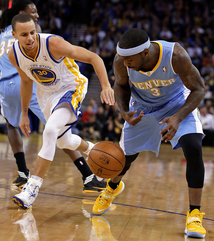 . Denver Nuggets\' Ty Lawson, right, and Golden State Warriors\' Stephen Curry chase a loose ball during the first half of an NBA basketball game Wednesday, Jan. 15, 2014, in Oakland, Calif. (AP Photo/Ben Margot)