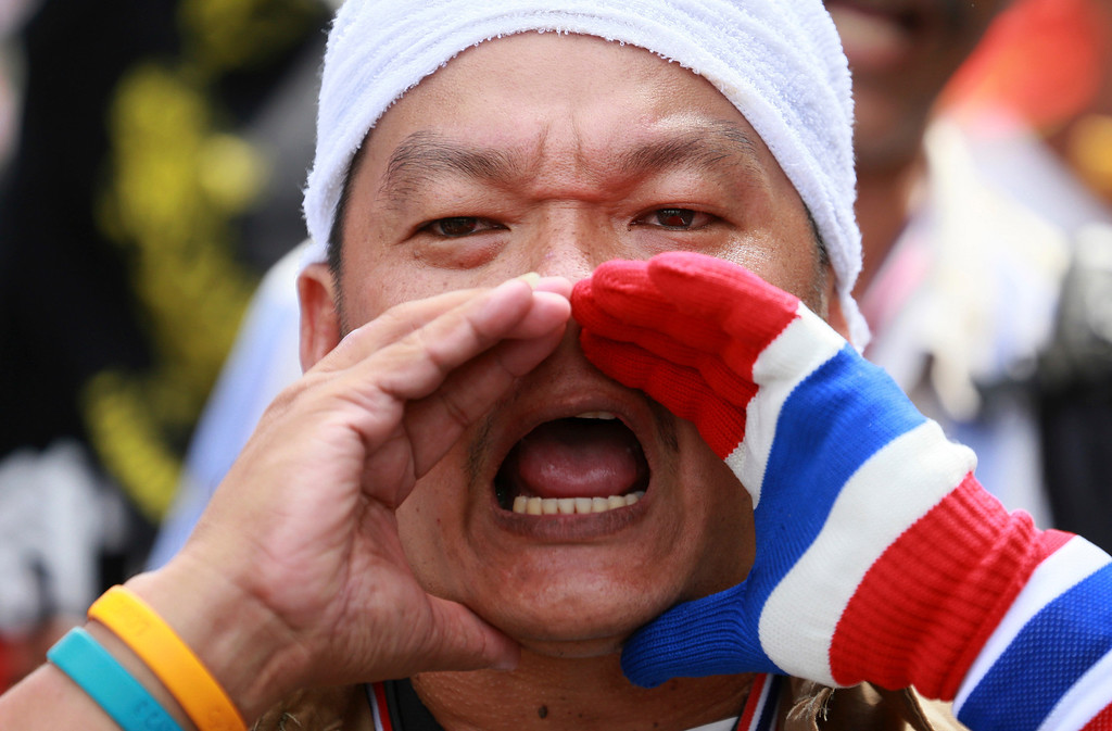 . An anti-government protester shouts slogans during gathering outside Interior Ministry in Bangkok, Thailand, Tuesday, Nov. 26, 2013. Protesters forced the closure of several government ministries Tuesday and vowed to take control of state offices nationwide in a bid to oust Prime Minister Yingluck Shinawatra, escalating the biggest challenge she has faced since taking office. (AP Photo/Wason Wnnichakorn)