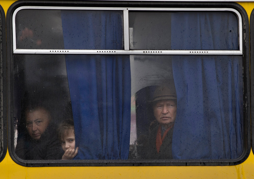 . People in a passing bus watch a rally against the breakup of the country in Simferopol, Ukraine on Friday, March 7, 2014. For the ethnic Ukrainians and Tatars who are the minority in the strategic peninsula, it is fear that dominates days before Crimea votes in a referendum on joining Russia. (AP Photo/Vadim Ghirda, File)