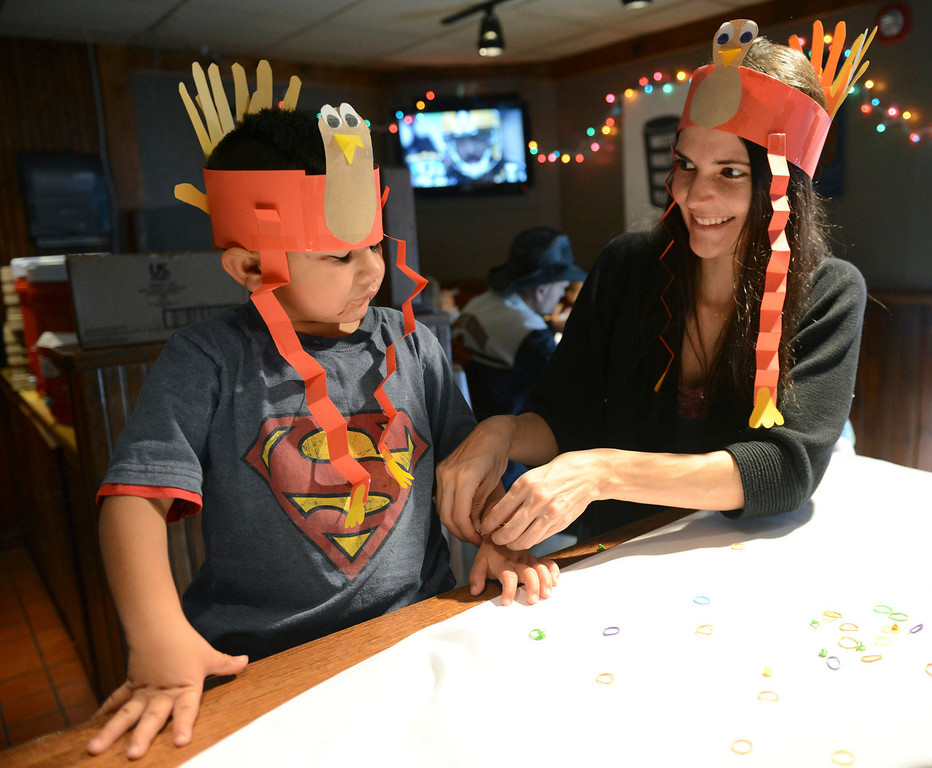 . Volunteer Natalie Waldrip puts a bracelet on Damian Lavitia, 3, during the annual OUR Center Thanksgiving meal served at Old Chicago, 1805 Industrial Circle, Thursday Nov. 28, 2013. Several hundred people were expected to be served this year. (Lewis Geyer/Times-Call)
