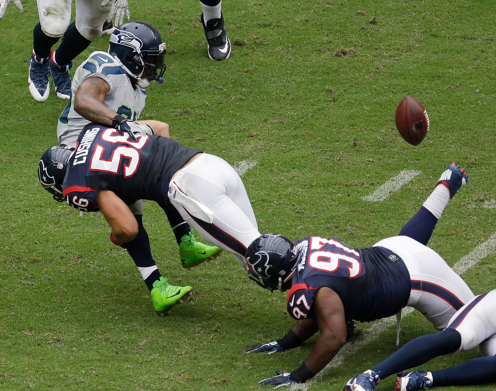 . Seattle Seahawks\' Marshawn Lynch, left, fumbles the ball as he is hit by Houston Texans\' Brian Cushing (56) during the second quarter an NFL football game on Sunday, Sept. 29, 2013, in Houston. Houston recovered the ball. (AP Photo/David J. Phillip)