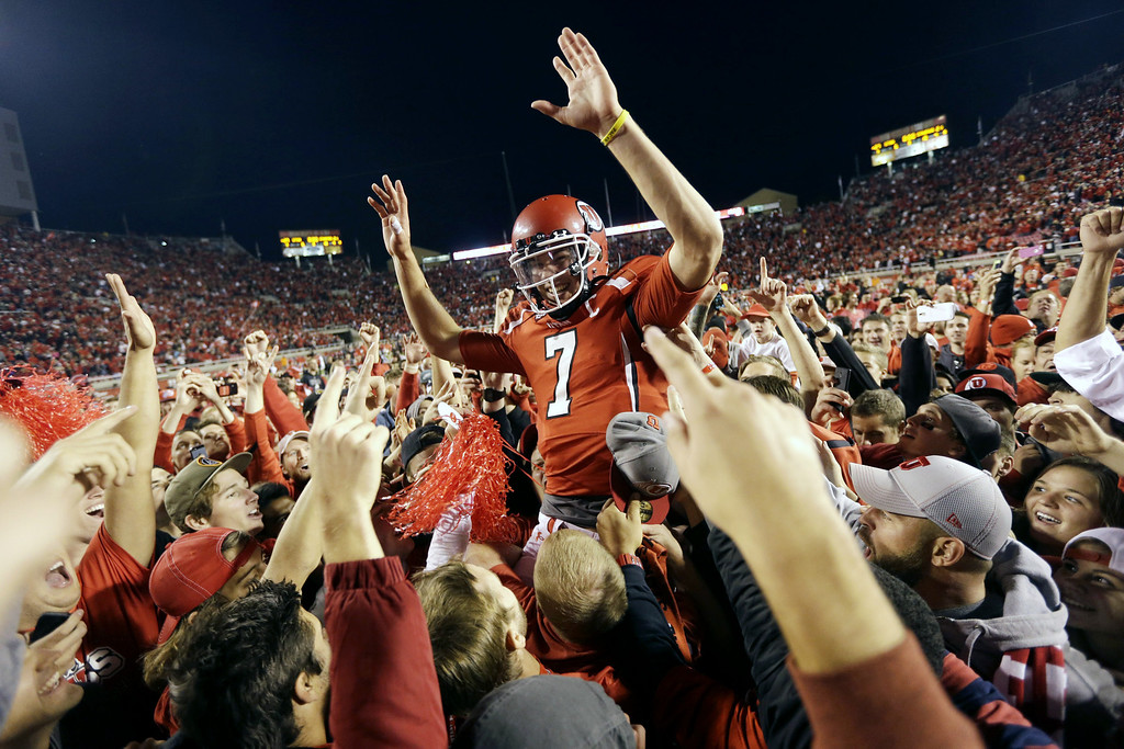 . Utah quarterback Travis Wilson (7) is hoisted to the air by Utah fans after defeating Stanford 27-21 during an NCAA college football game on Saturday, Oct. 12, 2013, in Salt Lake City. (AP Photo/Rick Bowmer)