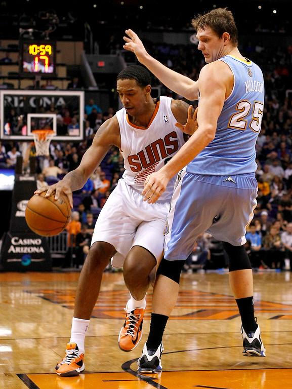 . Phoenix Suns forward Channing Frye, left, drives on Denver Nuggets center Timofey Mozgov (25) in the third quarter of an NBA basketball game, Sunday, Jan. 19, 2014, in Phoenix. (AP Photo/Rick Scuteri)