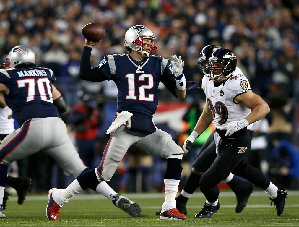 . New England Patriots quarterback Tom Brady (12) passes under pressure from Baltimore Ravens outside linebacker Paul Kruger (99) in the first quarter of the NFL AFC Championship football game in Foxborough, Massachusetts, January 20, 2013. REUTERS/Mike Segar