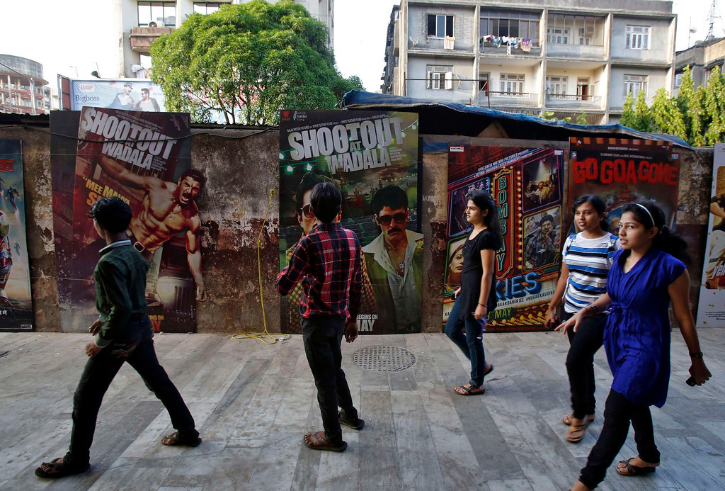 ". People walk past Bollywood film posters in Mumbai April 14, 2013. Indian cinema marks 100 years since Dhundiraj Govind Phalke\'s black-and-white silent film ""Raja Harishchandra\"" (King Harishchandra) held audiences spellbound at its first public screening on May 3, 1913, in Mumbai. Indian cinema, with its subset of Bollywood for Hindi-language films, is now a billion-dollar industry that makes more than a thousand films a year in several languages. It is worth 112.4 billion rupees (over $2 billion) and leads the world in terms of films produced and tickets sold. Picture taken April 14, 2013. REUTERS/Vivek Prakash"