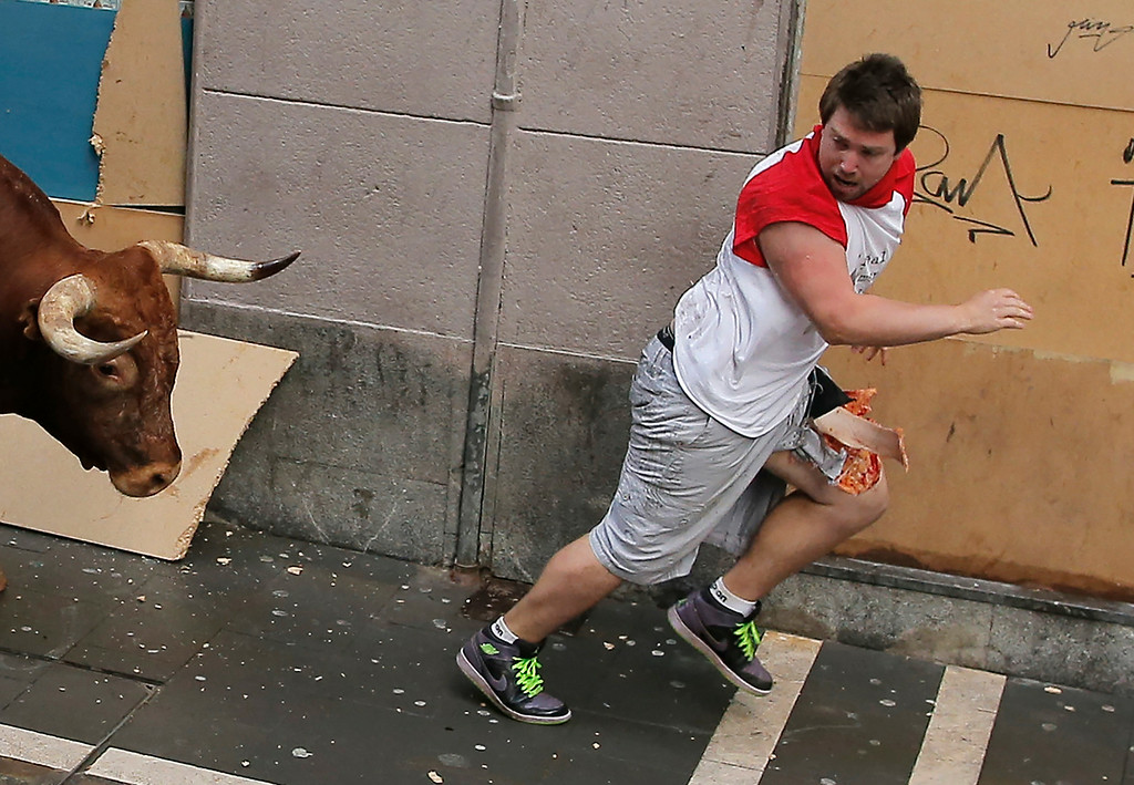 . A reveller runs with his leg injured after he was gored by a Miura fighting bull during the running of the bulls at the San Fermin festival, in Pamplona, Spain, Monday, July 14, 2014.  (AP Photo/Andres Kudacki)