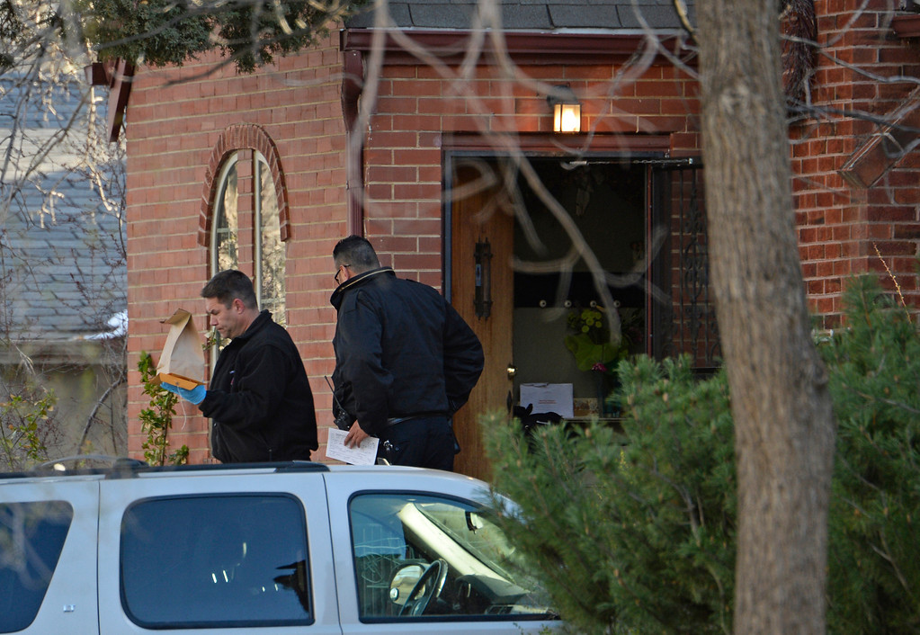 . A man carries out evidence as Denver police investigate a homicide at a home in the 2100 block of South Saint Paul Street in Denver, Tuesday, April 15, 2014. A woman was found dead in a home near the University of Denver Monday night. (Photo by RJ Sangosti/The Denver Post)